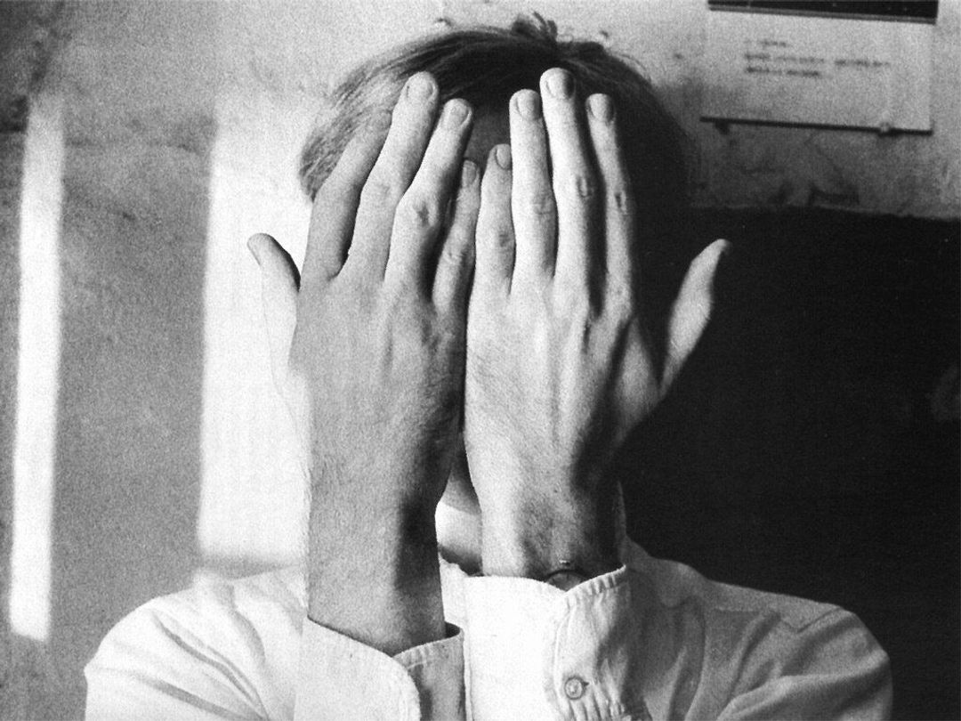 Person with hands over his face, photo by Duane Michals.