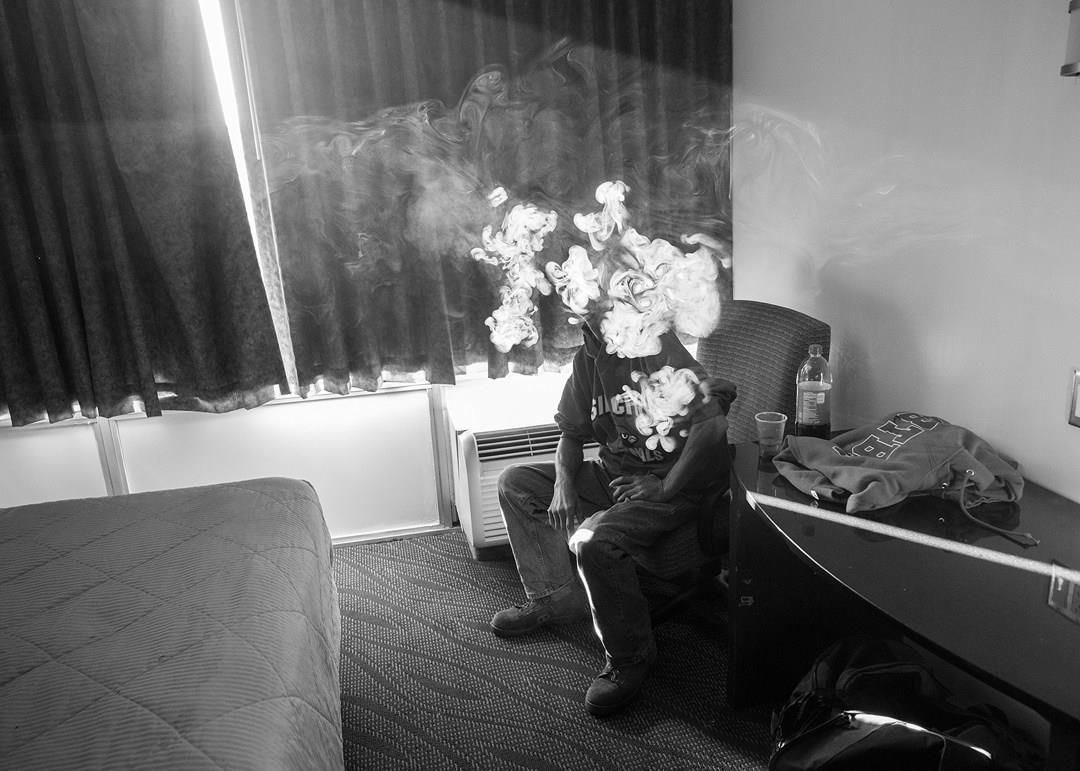 Black and white, Bob Mulcahey (50) smokes in his room of the Kings Inn, where Veterans Affairs has placed him temporarily while they address permanent housing for him. Photographer: Todd R Darling