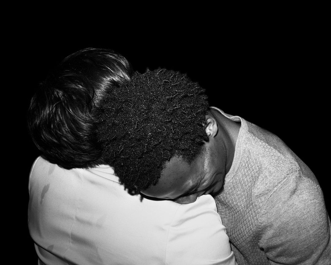Black and white, two men in tshirts intimately embracing with heads on shoulders. Shot taken from above with high flash.