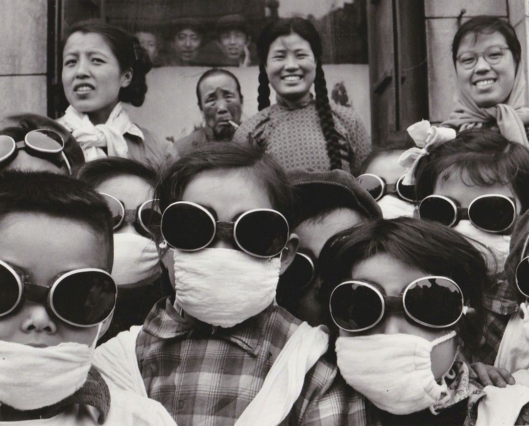 Vintage silver print taken by Agnes Varda of a bunch of Chinese children wearing goggles and masks to prepare to spend time in the Gobi desert. Adults standing behind them, perhaps teachers or parents.