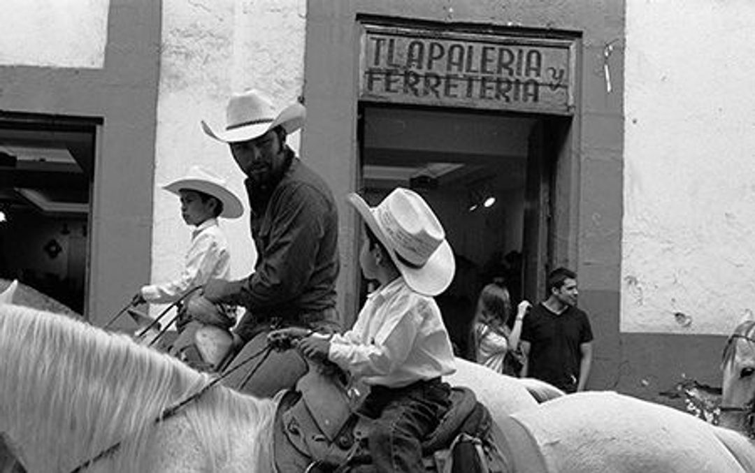"""An adult male cowboy on a horse, talking to a child cowboy on another horse. A sign behind them says """"Apaleria Ferreira""""."""