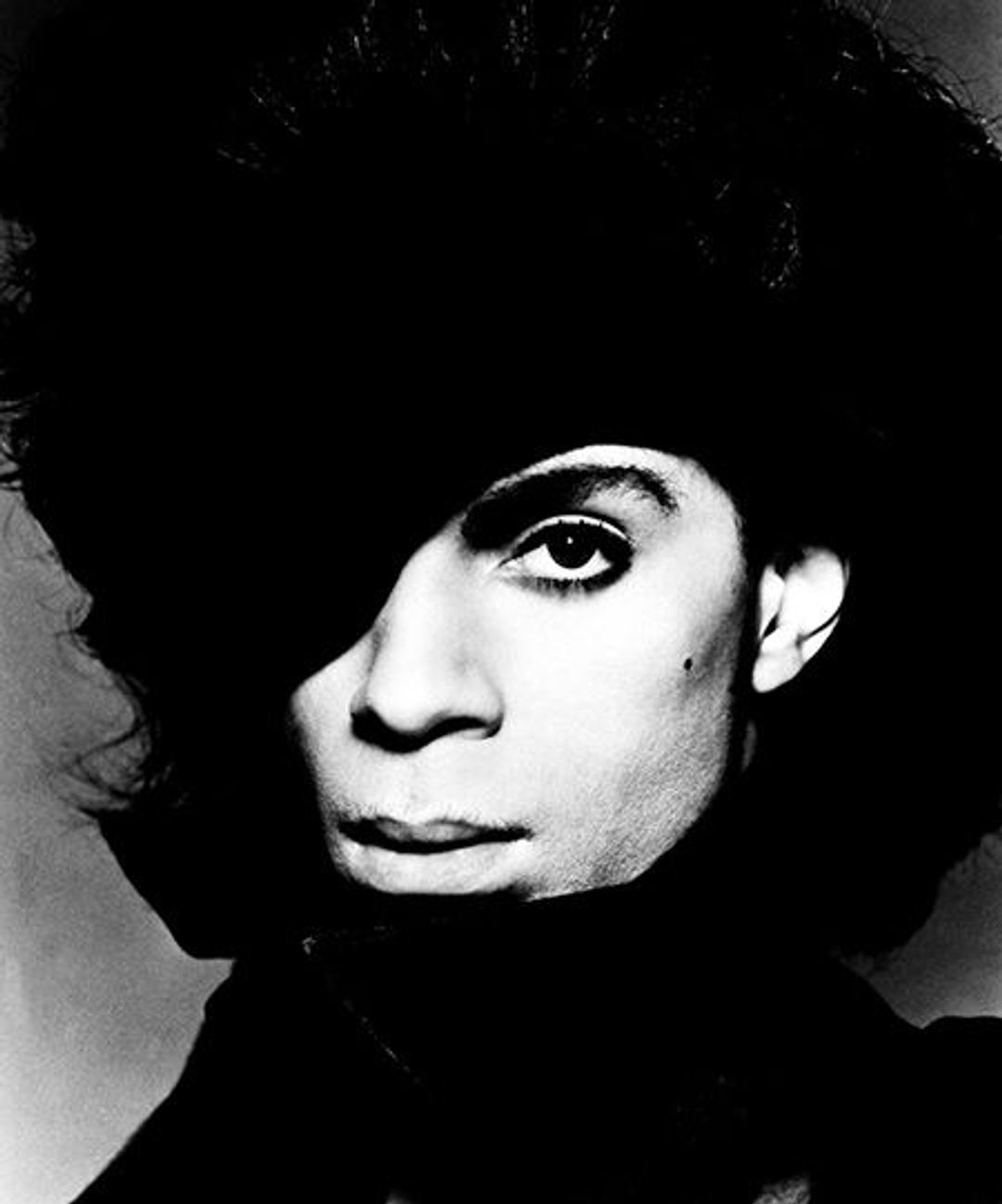 A heavily contrasted photo of Prince's face. A mole on his cheek. Stone cheekbones. He's possibly wearing a large black hat but the light's too dark to see.