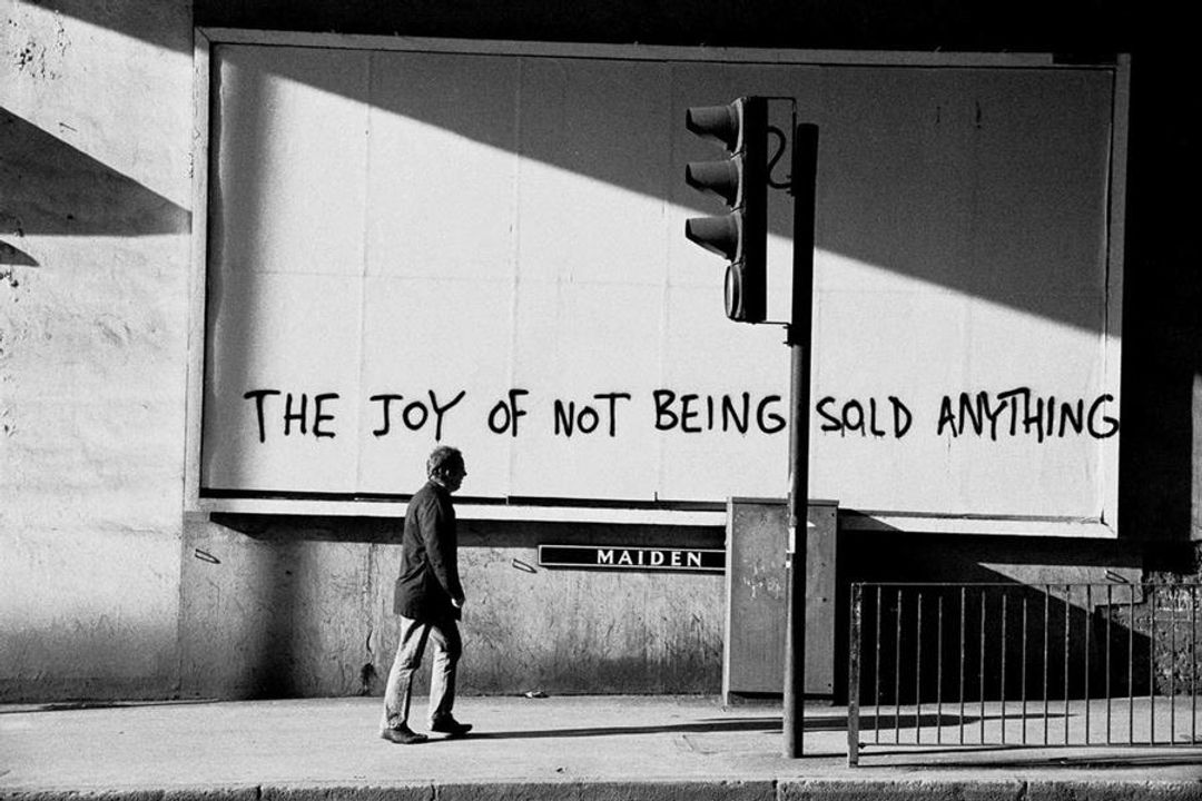 """A person walking along a footpath. Spray painted onto the wall beside them: """"THE JOY OF NOT BEING SOLD ANYTHING""""."""